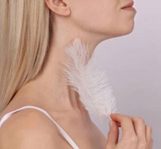 Женщина гладит шею пером