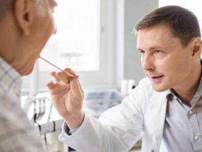 Терапевт осматривает горло пациента