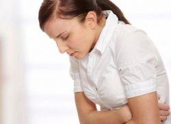 Женщина в белой рубашке корчится от боли